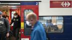 Pendler und Pendlerinnen mit und ohne Schutzmasken in einer S-Bahn in Zürich.