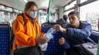 In Genf verteilt eine Mitarbeiterin des öffentlichen Verkehrs Masken.