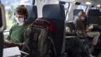 Eine junge Frau sitzt im Zug und trägt eine Schutzmaske.