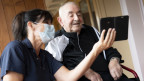 Das Bild zeigt einen Mann im Altersheim, der mit einer Betreuerin auf ein Handy schaut.
