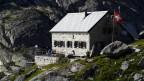Haus in den Bergen, Menschen sitzen auf der Terrasse.