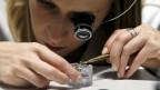 Eine Uhrmacherin der Marke Jaeger-LeCoultre montiert ein Uhrwerk.