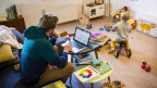 Symbolbild. Ein Mann arbeitet im Homeoffice und kümmert sich gleichzeitig um sein Kind.