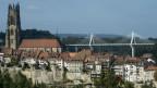 Das Bild zeigt im Vordergrund die Stadt Freibburg mit der Kathedrale und im Hintergrund die neue Schrägseilbrücke