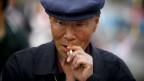 Porträt eines alten Chinesen mit gebräuntem faltigen Gesicht und Beret auf dem Kopf, eine Zigarette im Mund, die Finger rundherum.