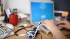 Ein Kopfhörer und ein Laptop auf einem Pult, Hände auf der Tastatur, der Bildschirm des Laptops zeigt verschwommen die Startseite von Skype.