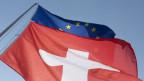 Schweizer Fahne und EU-Fahne.