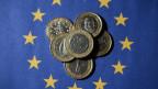 Münzen auf einer EU-Flagge.