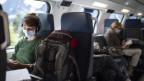 Passagiere sitzen mit Maske im Zug.
