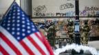 Hinter einer USA-Flagge stehen mehrere Soldaten, einer von ihnen hat eine Waffe im Anschlag, es sind Rauchschwaden zu sehen.