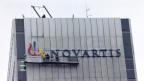 Der neue Novartis-Schriftzug wird am Hauptsitz montiert