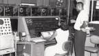 Zwei Menschen bedienen eine grosse Rechenmaschine