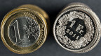 Ein-Euro- und ein Ein-Franken-Stücke liegen auf dunkelgrauer Fläche.
