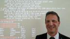 Diego Schmidlin leitet das Ruag-Trainingszentrum für Cyber-Sicherheit in Bern. Er steht vor einer Wand mit Codes, mithilfe derer man Cyber-Kriminelle abwehren kann.