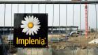 Das Logo der Bau-Unternehmung Implenia an einer Baustelle.