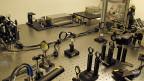 Auf einem Metalltisch sind Dutzende kleiner Linsen und Spiegel angebracht. Was aussieht wie ein unaufgeräumter Tisch in einem Tüftlerlabor, ist eine Apparatur, die es in der Schweiz nur ein einziges Mal gibt: Mit ihr lässt sich die Dicke einer beschichteten Glasplatte messen.