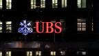 Blick auf ein UBS-Gebäude bei Nacht.