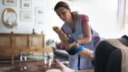 Eine Spitex Mitarbeiterin der Spitex Thun zieht einer Klientin einen Stützstrumpf an.