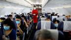 Flugbegleiterin und Passagiere in einem Flugzeug. Symbolbild.