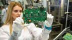 Mitarbeiterin bei Continental mit einer Leiterplatte mit der Steuerungs-Elektronik.