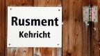 Ein Hinweisschild in den beiden Sprachen Romanisch und Deutsch hängt an einer Kehrichtsammelstelle in Stierva hoch über dem bündnerischen Albulatal.