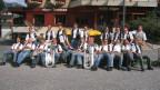 Die Musikantinnen und Musikanten mit ihren Instrumenten in entspannter Pose vor einem Restaurant.
