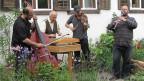 Die vier Musikanten spielen im Garten Kontrabass, Hackbrett, Geige und Klarinette.