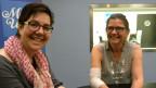 Karin Kobler sitzt mit Gisela Schmidli an einem grossen langen Tisch vor dem Studio von SRF Musikwelle.