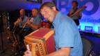 Im Vordergrund ein Schwyzerörgeli-Spieler, hinter ihm weitere Musiker.