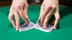 Zwei Hände, die zwei Stapel Karten ineinander mischen.