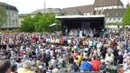 Chor in weissen, wallender Kleidern auf einer Bühne (mit Zeltdach) mitten auf einem grossen Platz in Basel, umringt von hunderten von Konzertbesuchern.