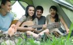 Zwei Mädchen und zwei Jungs im Ferienlager. Sie sitzen im Zelt und singen zusammen mit Gitarrenbegleitung.