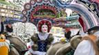 Bunt und kunstvoll maskierte Männer und Frauen während eines Umzugs.