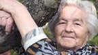 Eine alte zufriedene Frau umarmt einen dicken Baumast.