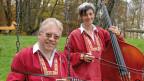 Martin Schütz mit Fränzi von Chueli Musig in roten Sennenchutteli. Martin sitzt auf einer Schaukel, die beiden halten ihre Instrumente - er ein Schwyzerörgeli, sie einen Kontrabass - in Händen.