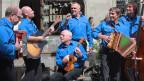 Die sechs Musikanten in blauen Hemden musizieren in einer Gasse.