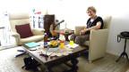Edith Trefzer in ihrem Wohnzimmer sitzt auf weissem Sessel auf dem Tisch vor ihr steht ein Mikrophon.