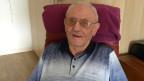 Der Rentner mit Brille sitzt in einem braunen Ledersessel.