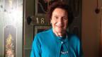 Die Schriftstellerin trägt einen blauen Pullover mit Strickjacke und steht vor einem Schrank mit Bauernmalerei.