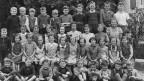 Schwarz-Weiss Fotografie von einer Schulklasse. Die Schülerinnen und Schülern posieren in vier Reihen für den Fotografen.