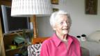 Alice Marti in ihrem Zimmer im Altersheim Lyss. Darin stehen ein Einzelbett, ein Holztisch mit gehäkelter Tischdecke sowie eine alte Stehlampe und ein Rollator. Auf dem Bettüberwurf liegen eine Stoffkatze und ein weiteres Stofftier. Frau Marti sitzt am Tisch und trägt ein lachsfarbenes Hemd mit Kragen.
