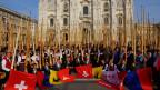 hunderte von Alphornisten vor dem Mailänder Dom. davor sitzen Fahnenschwinger mit Kantons- und Schweizerfahnen.