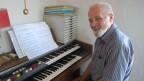 Ein Mann sitzt in seinem Wohnzimmer am Klavier.