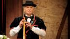 Der Alphornspieler trägt eine schwarze Sennenkutte über einem weissen Hemd und einen schwarzen Hut.