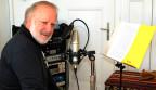 Peter Reber sitzt in seinem kleinen Studio vor einem Mikrofon, hinter dem ein Notenständer mit einem Manuskript steht.