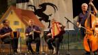 Ländlerkapelle während Auftritt auf der Bühne. Im Hintergrund Kulisse einer ehemaligen Theateraufführung