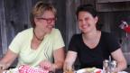 Die zwei Frauen sitzen vor vollen Tellern auf der Terrasse der Gartenwirtschaft.