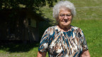 Die ältere Frau mit grauen Haaren und Brille auf einem Platz vor Wiese und Sträuchern.