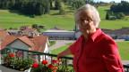 Die ältere Frau steht an einem sonnigen Tag auf dem Balkon.