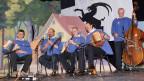 Zwei Schwyzerörgeler, zwei Klarinettisten und ein Bassgeiger in blauen Sennenkutten während eines Auftritts.